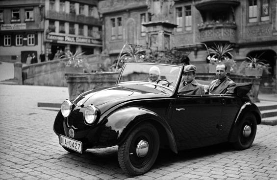 Ferry Porsche 1936 am Steuer des Volkswagen-Prototypen (V2) auf dem Marktplatz in Tübingen (Foto: Porsche)
